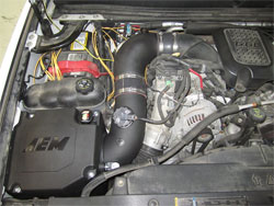 AEM inlet temperature testing in progress. Engine photo of a 2007 Chevy 2500HD 6.6L Duramax with 21-9033DS installed along with yellow test wires attached to temperature sensors.
