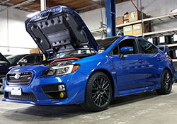 The 2015 and 2016 Subaru WRX STi, shown here in WR Blue Pearl paint, is powered by the EJ257 intercooled and turbocharged engine and equipped with an AEM performance cold air intake