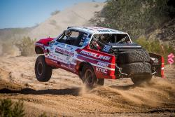 With clouds of dirt & dust racers drive thru in an off-road race proper filteration is critical
