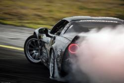 The distinctive C6 Corvette taillights peak through a cloud of tire smoke Photo by Valters Boze